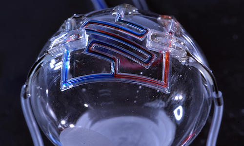 Microfluid channels three-dimensionally-printed on a curved surface.